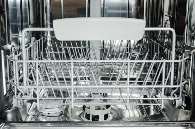 Feche acima da máquina de lavar louça vazia aberta. eletrodomésticos