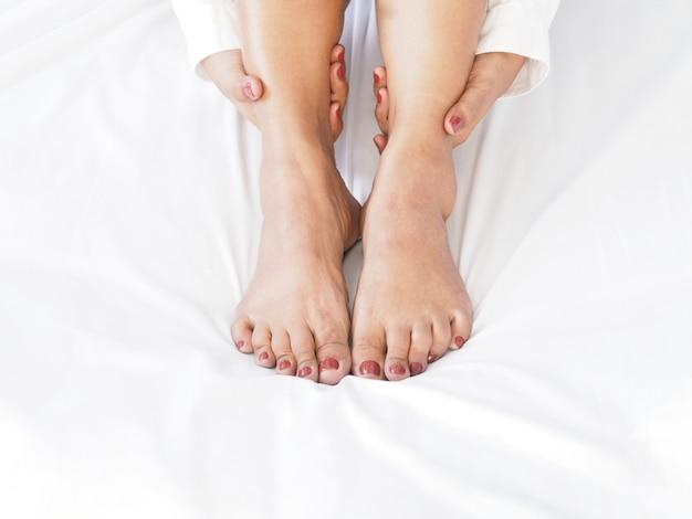 Feche acima da massagem do pé da mulher por si mesma.