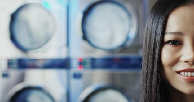 Feche acima da meia cara da mulher consideravelmente à moda nova asiática com bordos vermelhos e nos vidros amarelos que sorri à câmera na sala de serviço da lavanderia. retrato de uma linda garota feliz em máquinas de lavar.