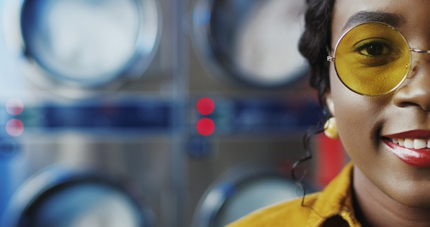 Feche acima da meia cara da mulher consideravelmente nova afro-americano à moda com bordos vermelhos e nos vidros amarelos que sorri à câmera na sala de serviço da lavanderia. retrato de uma menina bonita em máquinas de lavar.