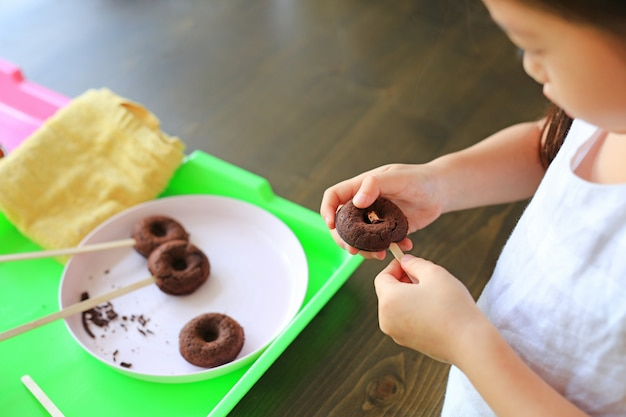 Feche acima da menina asiática pequena da criança na classe de processo de filhóses caseiros do chocolate.