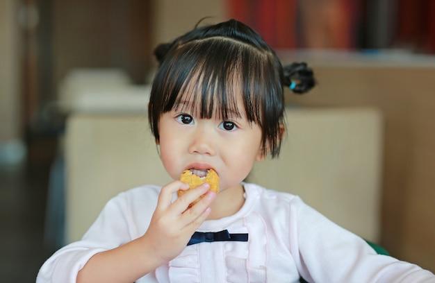 Feche acima da menina asiática pequena que come o frango frito no café.