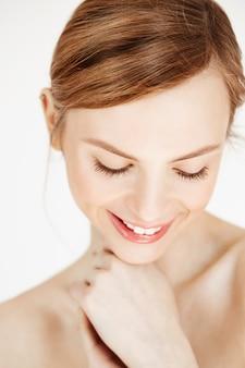 Feche acima da menina bonita nua tímida com a pele limpa e saudável, olhando para baixo sorrindo. conceito de spa e cosméticos de beleza.