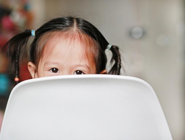 Feche acima da menina bonito evitam na parte de trás da cadeira plástica branca que olha a câmera.