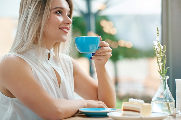 Feche acima da menina loura bonito que mantém a xícara de café fora, sorrindo.