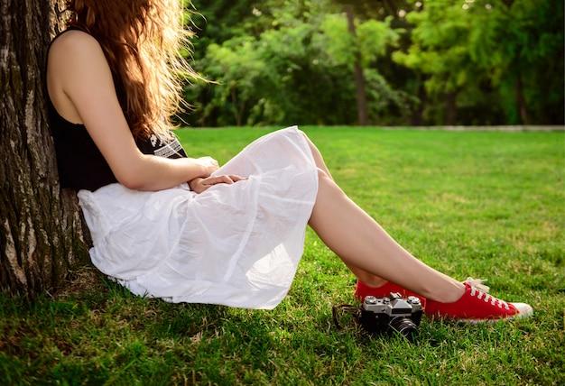 Feche acima da menina nos keds vermelhos que sentam-se na grama.