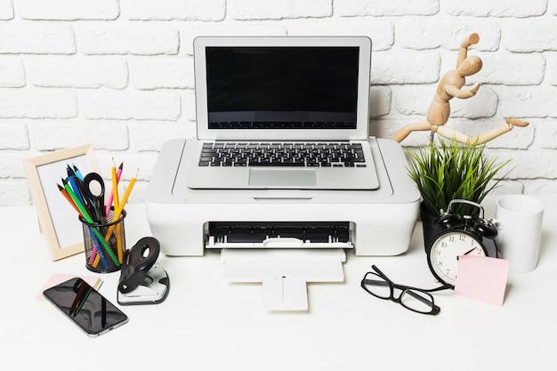 Feche acima da mesa de trabalho em casa com impressora e suprimentos