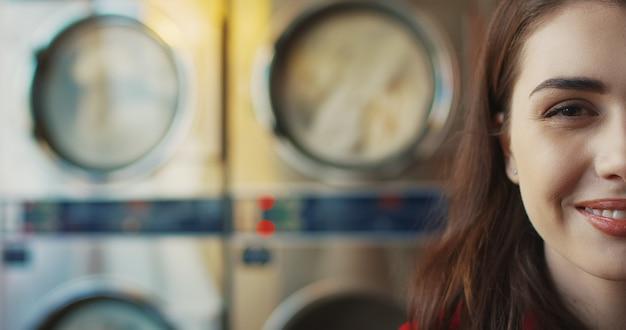 Feche acima da metade do rosto da mulher jovem e bonita caucasiana elegante com lábios vermelhos e óculos amarelos, sorrindo para a câmera na sala de serviço de lavanderia. retrato de uma linda garota feliz em máquinas de lavar.