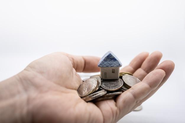Feche acima da mini casa do brinquedo sobre a pilha das moedas na mão do homem com branco.