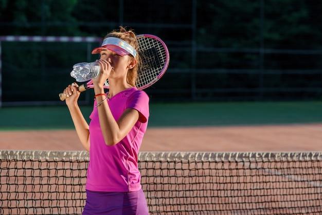 Feche acima da moça bonito na água potável desportiva do tampão da garrafa plástica após o treinamento duro do tênis no fundo exterior da corte no por do sol.