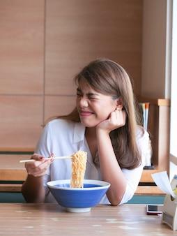 Feche acima da mulher asiática a cara furada usando hashis para comer o macarronete no restaurante.