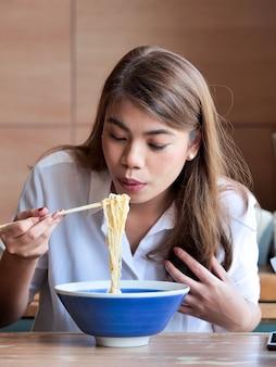 Feche acima da mulher asiática feliz que usa hashis para comer o macarronete no restaurante, conceito do tempo de almoço.