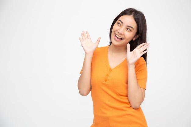Feche acima da mulher asiática nova gritando entusiasmada isolada