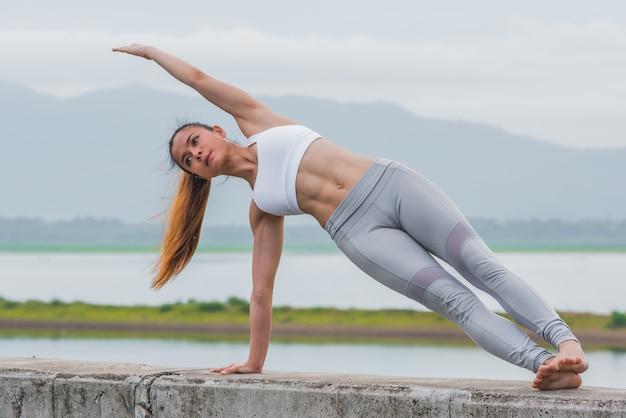 Feche acima da mulher asiática que faz o pose da ioga na praia.