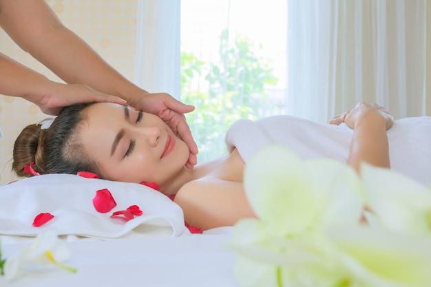 Feche acima da mulher bonita que tem a massagem principal no estilo de vida saudável da beleza do bem-estar do salão de beleza dos termas e no conceito do abrandamento.