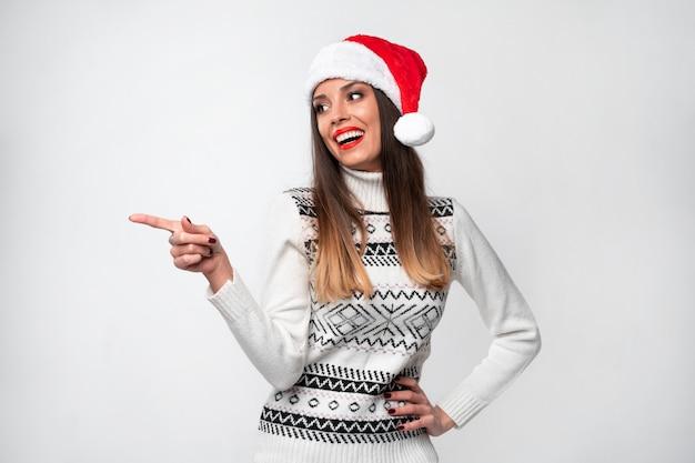 Feche acima da mulher caucasiano bonita do retrato no chapéu vermelho de santa na parede branca. conceito de ano novo de natal. dentes bonitos da mulher que sorriem lado positivo do dedo indicador mostrando