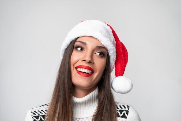 Feche acima da mulher caucasiano bonita do retrato no chapéu vermelho de santa na parede branca. conceito de ano novo de natal. dentes de mulher bonita sorrindo emoções positivas com espaço de cópia gratuita