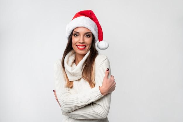 Feche acima da mulher caucasiano bonita do retrato no chapéu vermelho de santa na parede branca. conceito de ano novo de natal mulher bonita se abraça dentes sorrindo emoções positivas com espaço de cópia gratuita