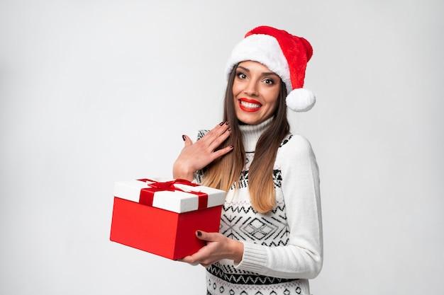 Feche acima da mulher caucasiano bonita do retrato no chapéu vermelho de santa na parede branca. conceito de ano novo de natal surpreendeu os dentes de mulher bonita sorrindo emoções positivas com caixa de presente vermelha
