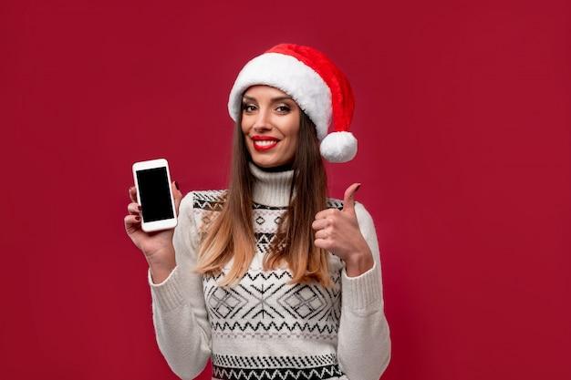 Feche acima da mulher caucasiano bonita do retrato no chapéu vermelho de santa na parede vermelha. conceito de ano novo de natal. dentes de mulher bonita sorrindo emoções positivas com espaço de cópia gratuita
