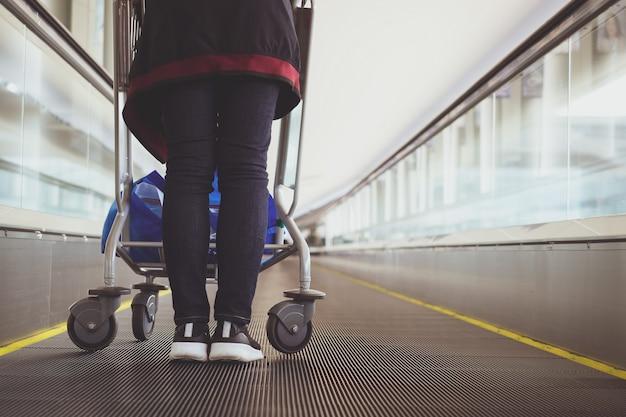 Feche acima da mulher com o trole da bagagem na escada rolante do aeroporto