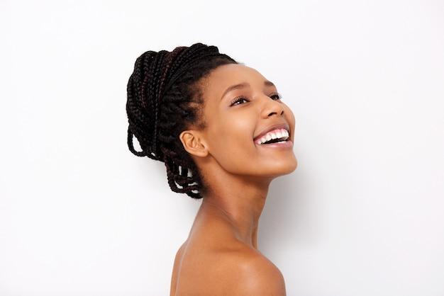 Feche acima da mulher consideravelmente africana que olha afastado e que sorri com ombros despidos