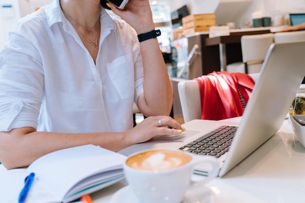 Feche acima da mulher de negócio das mãos que senta-se no escritório coworking e que datilografa em seu computador do teclado do portátil.