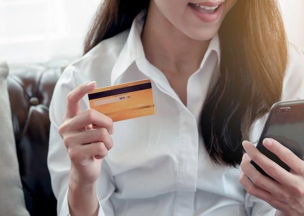 Feche acima da mulher de negócio feliz a usar o cartão de crédito para pagar pelo sucesso em linha da compra.