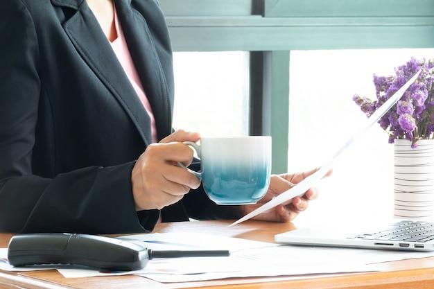 Feche acima da mulher de negócio que trabalha no escritório e faça a decisão no relatório das estatísticas da venda