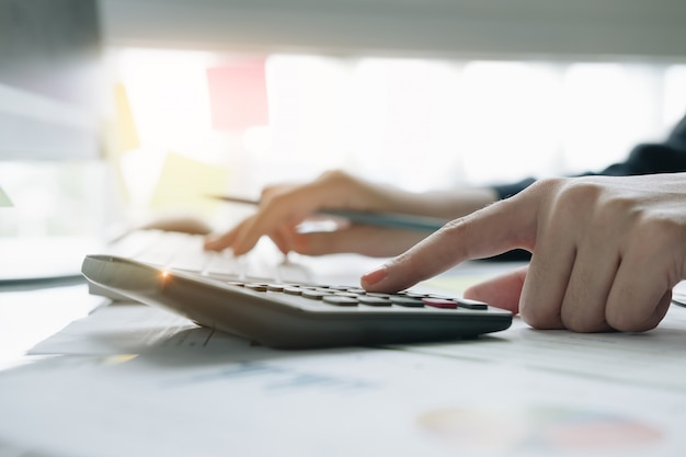 Feche acima da mulher de negócio que usa a calculadora e o portátil para fazem o financiamento da matemática na mesa de madeira no escritório e no fundo de trabalho do negócio
