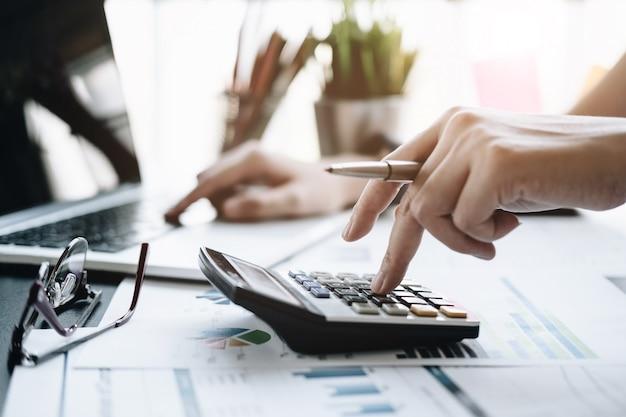 Feche acima da mulher de negócio que usa a calculadora e o portátil para fazer a finança da matemática