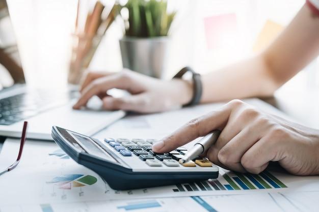 Feche acima da mulher de negócio que usa a calculadora e o portátil para fazer finanças da matemática na mesa de madeira no funcionamento do escritório e do negócio