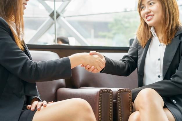 Feche acima da mulher de negócios de dois sorrisos que agita as mãos ao sentar-se na sala.