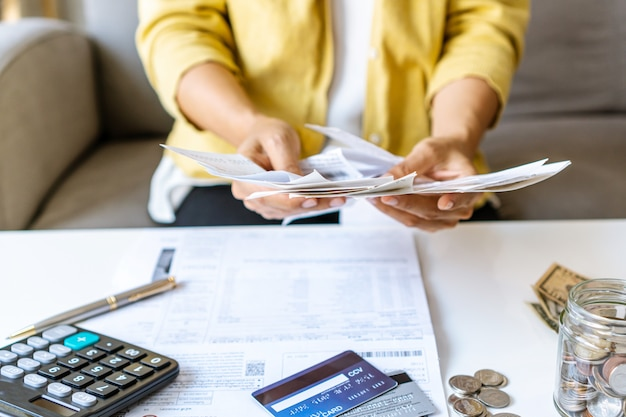 Feche acima da mulher de negócios que verifica contas e que calcula a despesa mensal em sua mesa. conceito de economia em casa. conceito de pagamento financeiro e parcelado.