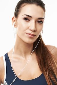 Feche acima da mulher desportivo nos fones de ouvido que levantam no branco.