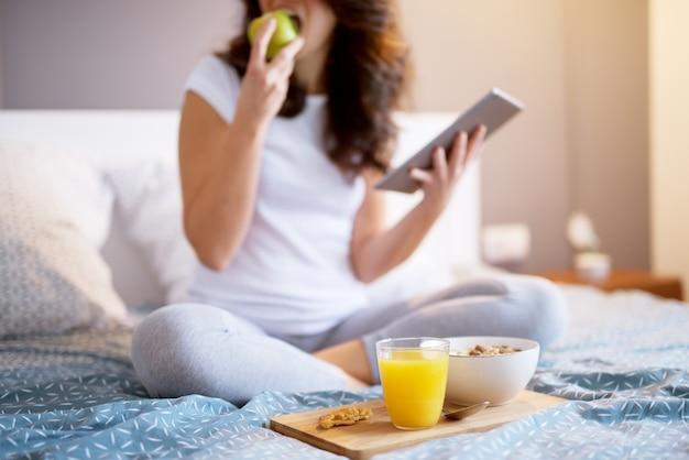 Feche acima da mulher envelhecida média atrativa de sorriso que senta-se na cama com uma maçã e que olha em uma tabuleta.
