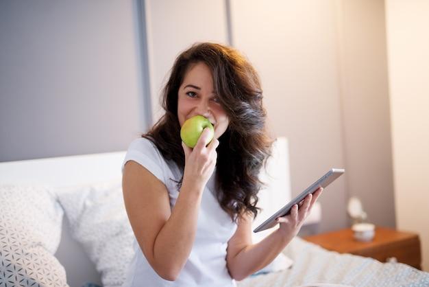 Feche acima da mulher envelhecida média bonita sorridente, sentada na cama com um tablet e morde uma maçã enquanto olha