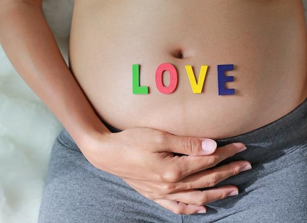 Feche acima da mulher gravida com palavra do amor na frente de sua barriga.