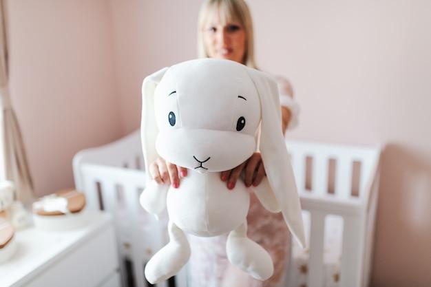 Feche acima da mulher gravida que guarda o brinquedo do coelho ao estar na sala do bebê.