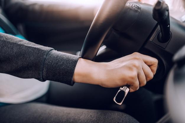 Feche acima da mulher gravida que liga o carro.