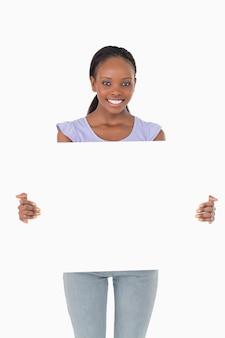 Feche acima da mulher que apresenta o espaço reservado no fundo branco