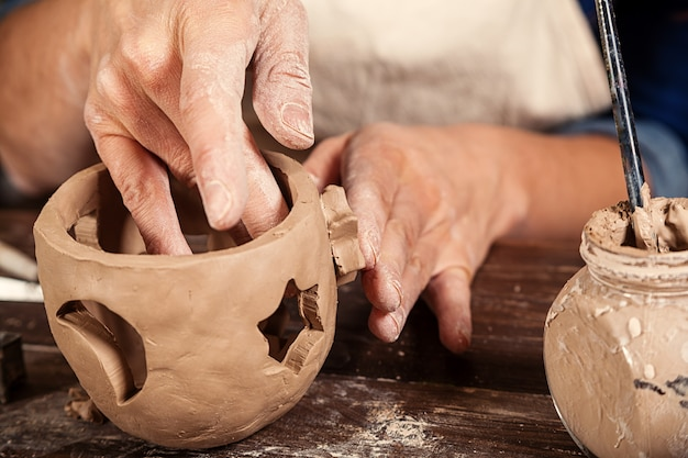 Feche acima da mulher que faz a cerâmica