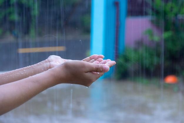 Feche acima da mulher que põe sua mão nas gotas de travamento da chuva da chuva, conceito da água.