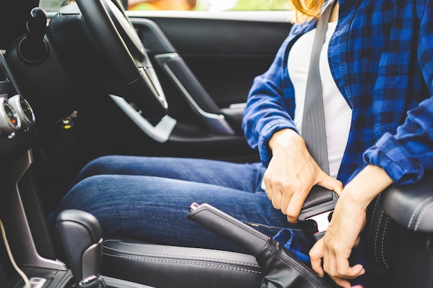 Feche acima da mulher que senta-se no banco de carro e no cinto de segurança da fixação, conceito da segurança do carro.