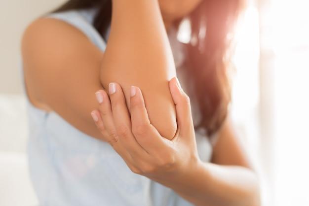 Feche acima da mulher que tem a dor no cotovelo ferido. conceito de cuidados de saúde e dor de braço.