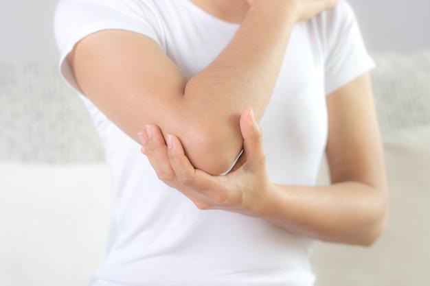 Feche acima da mulher que tem a dor no cotovelo ferido.