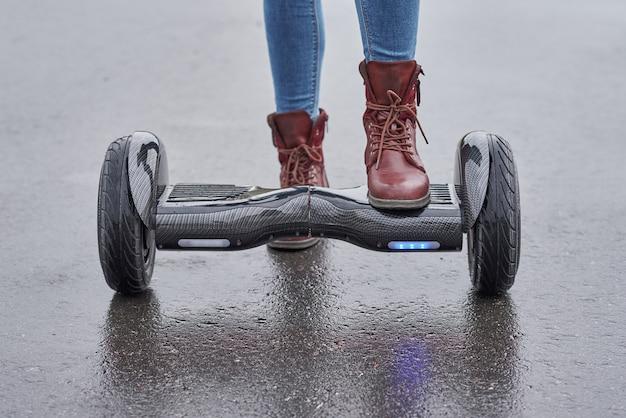 Feche acima da mulher que usa o hoverboard na estrada asfaltada. pés na scooter elétrica ao ar livre
