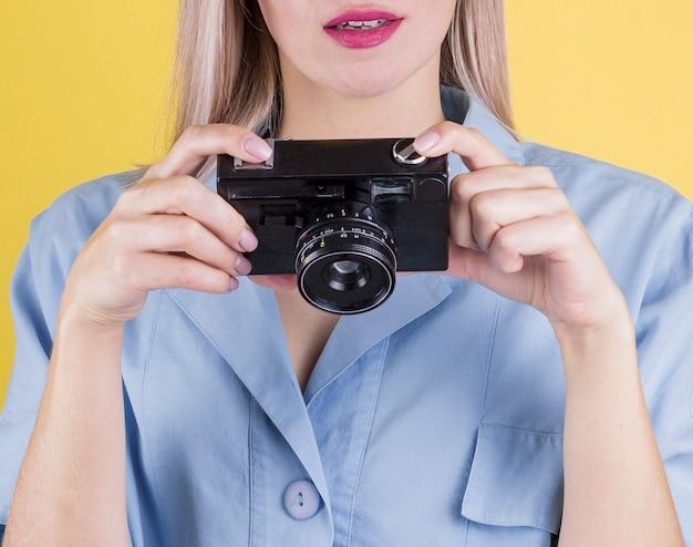 Feche acima da mulher segurando uma câmera