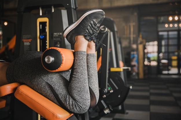 Feche acima da mulher sentada do exercício da máquina da onda da perna do gym da vista em interno. conceito da saúde.