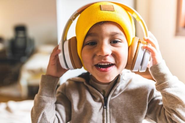Feche acima da música de escuta do menino latino-americano em fones de ouvido.
